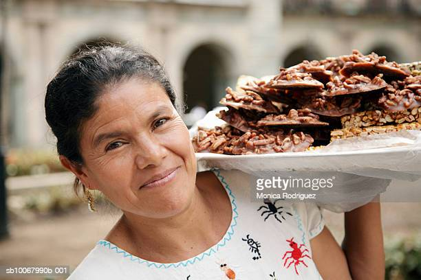 Mexico, Oaxaca, mature woman carrying tray with chocolate and nut candy, portrait