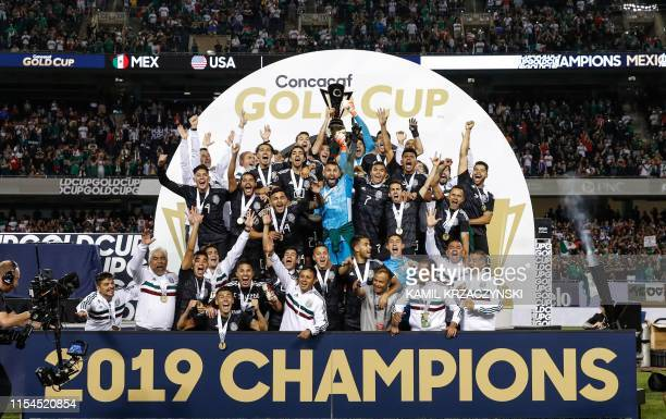 Mexico players and coaches celebrate with the Gold Cup after beating the US during the 2019 Concacaf Gold Cup final football match between USA and...