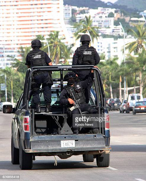 Mexico - Police officers patrol along a street near a beach in Acapulco, a Pacific resort in Mexico, on Nov. 19, 2013.