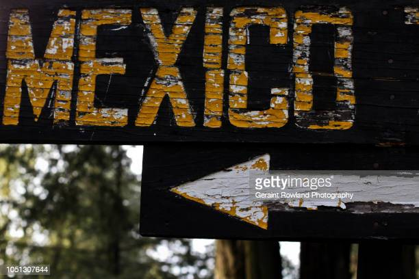 mexico this way - immigrants crossing sign stock photos and pictures
