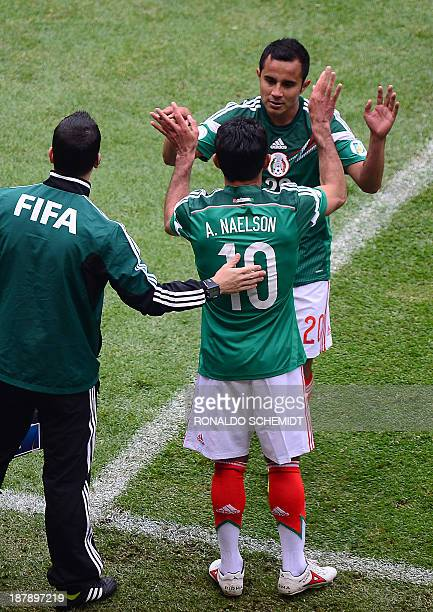 Mexico's Antonio Naelson substitutes midfielder Luis Montes during their FIFA World Cup intercontinental playoff football match in Mexico City on...