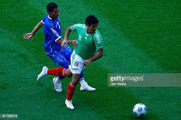 Mexicos' Carlos Vela vies for the ball with Marvin Gonzalez of El Salvador during a 2010 FIFA World Cup qualifying soccer match at the Azteca Stadium...
