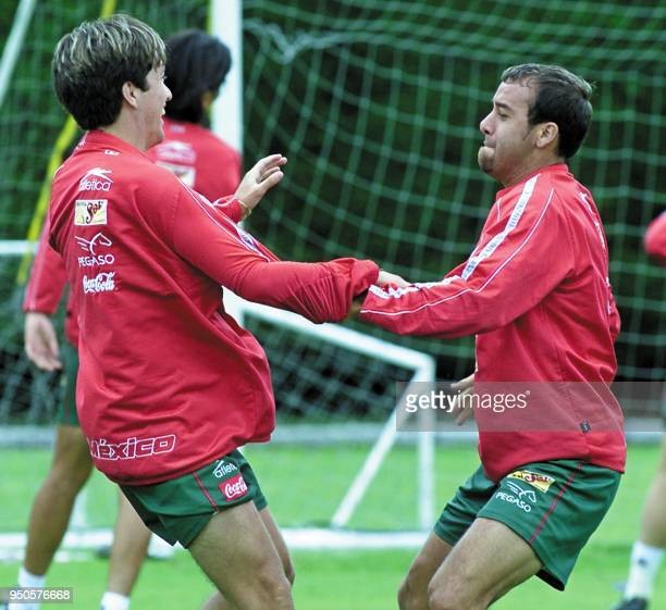 Mexico's Cesario Victorino and Johan Rodriguez do warm up exercises during a practice session at Carmel Club in Bogota 28 July 2001 Mexico is...