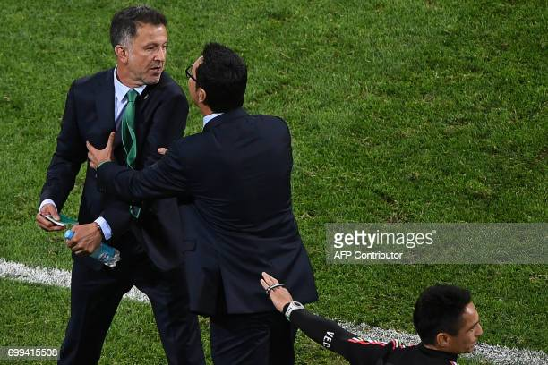 Mexico's Colombian coach Juan Carlos Osorio is held back during the 2017 Confederations Cup group A football match between Mexico and New Zealand at...