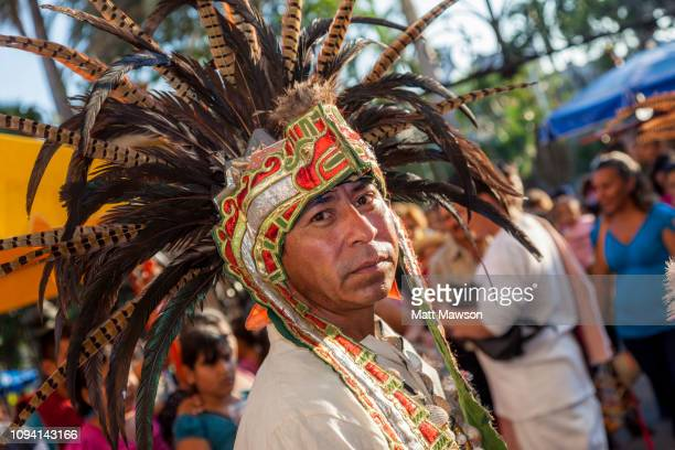 mexico's day of the virgin of guadalupe and an man in pre-colombian indian dress. - festival de la virgen de guadalupe fotografías e imágenes de stock