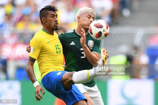 Mexico's defender Carlos Salcedo vies for the ball with Brazil's midfielder Paulinho during the Russia 2018 World Cup round of 16 football match...