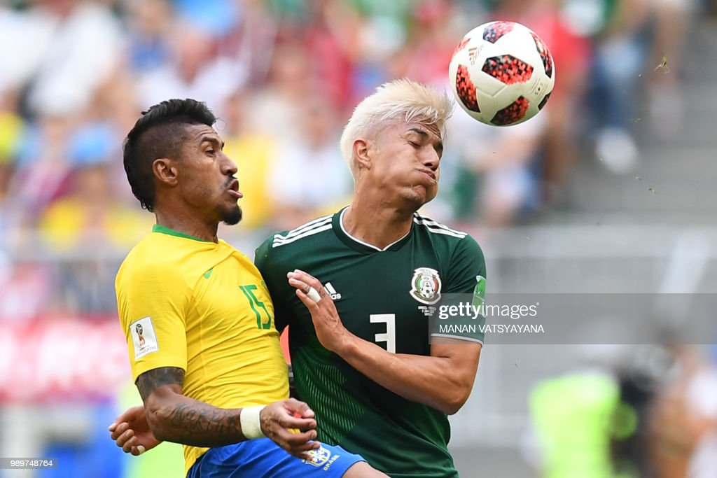 TOPSHOT - Mexico's defender Carlos Salcedo (R) vies for the ball with Brazil's midfielder Paulinho (L) during the Russia 2018 World Cup round of 16 football match between Brazil and Mexico at the Samara Arena in Samara on July 2, 2018. (Photo by MANAN VATSYAYANA / AFP) / RESTRICTED