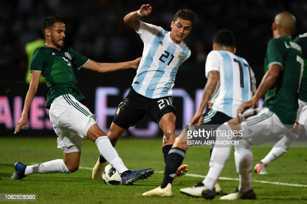 Mexico's defender Diego Reyes vies for the ball with Argentina's forward Paulo Dybala during their friendly football match at Mario Alberto Kempes...