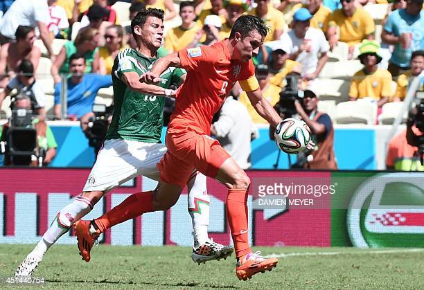 Mexico's defender Hector Moreno and Netherlands' forward and captain Robin van Persie vie for the ball during a Round of 16 football match between...