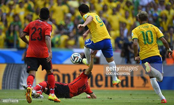 Mexico's defender Hector Moreno vies with Brazil's forward Fred during a Group A football match between Brazil and Mexico in the Castelao Stadium in...