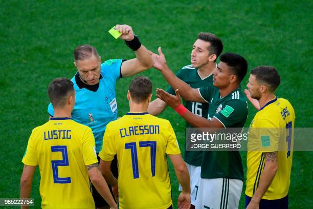 Mexico's defender Jesus Gallardo is shown a yellow card by Argentine referee Nestor Pitana during the Russia 2018 World Cup Group F football match...