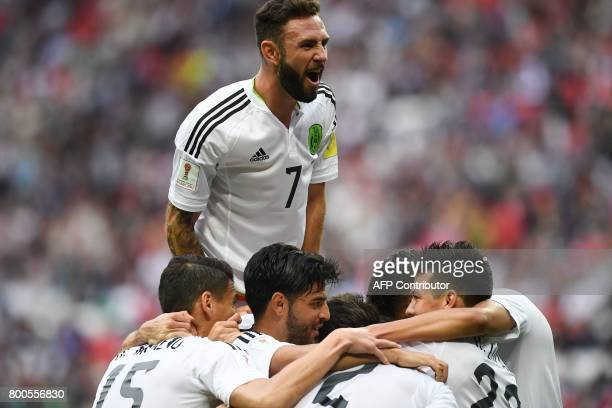 Mexico's defender Nestor Araujo celebrates with teammate Mexico's midfielder Miguel Layun and other players after scoring the team's first goal...