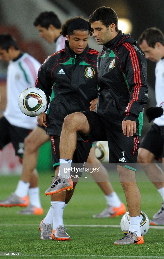 Mexico's defender Rafael Marquez plays with the ball in front of Mexico's striker Giovani dos Santos (L) at Peter Mokaba stadium in Polokwane during a training session on June 16, 2010. Mexico will face France next June 17 in their Group A game of the World Cup 2010 in Polokwane.
