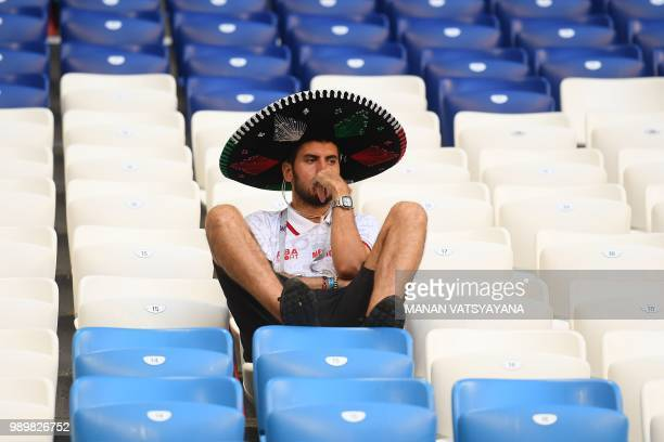 Mexico's fan reacts at the end of the Russia 2018 World Cup round of 16 football match between Brazil and Mexico at the Samara Arena in Samara on...