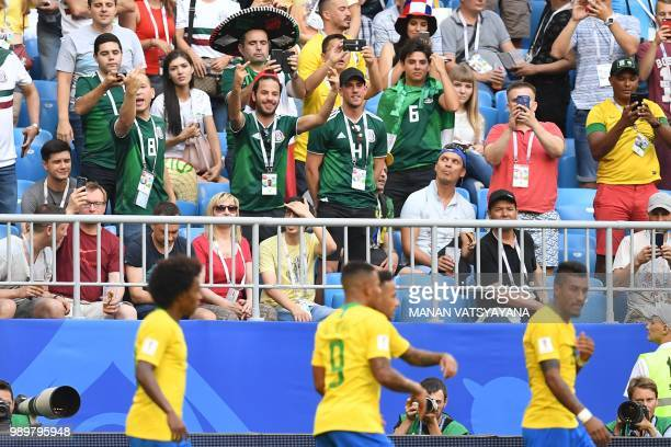 Mexico's fans react as Brazil's team players celebrate after scoring a goal during the Russia 2018 World Cup round of 16 football match between...