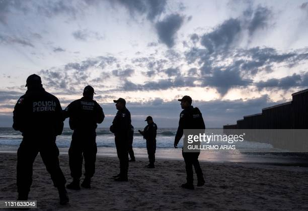 TOPSHOT Mexico's Federal Police officers stand guard near the USMexico border fence in Playas de Tijuana after a large group of Central American...
