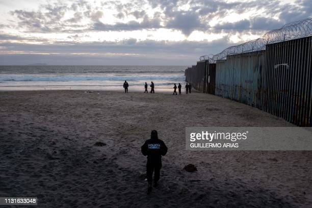 Mexico's Federal Police officers stand guard near the USMexico border fence in Playas de Tijuana after a large group of Central American migrants...