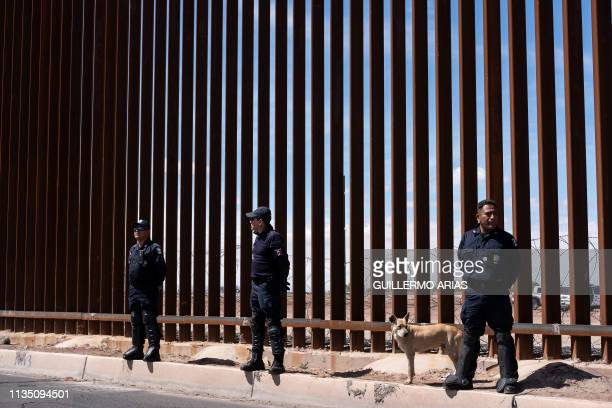 TOPSHOT Mexico's federal police stand guard at the USMexico border fence as US President Donald Trump visits Calexico California as seen from...