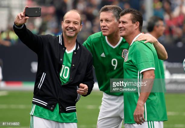 Mexico's former players Luis Garcia Ricardo Pelaez and Ramon Ramirez pose for a selfie before an exhibition football match between Mexico and Germany...