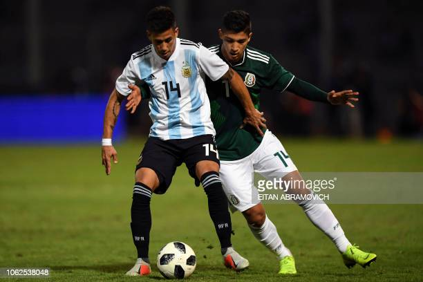 Mexico's forward Angel Zaldivar vies for the ball with Argentina's midfielder Maximiliano Meza during their friendly football match at Mario Alberto...