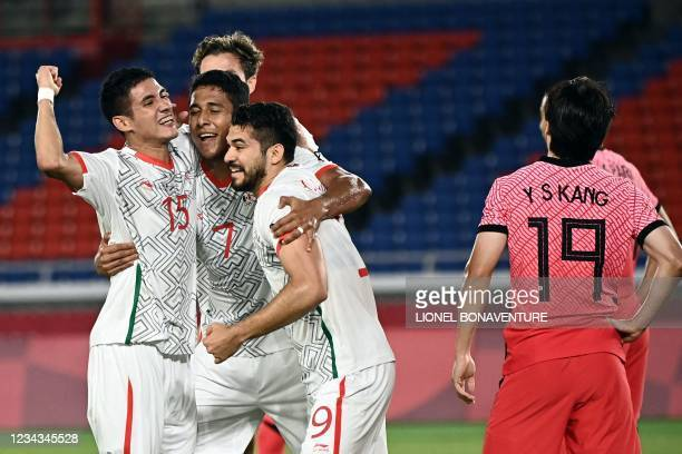 Mexico's forward Henry Martin celebrates with teammates after scoring a goal during the Tokyo 2020 Olympic Games men's quarter-final football match...