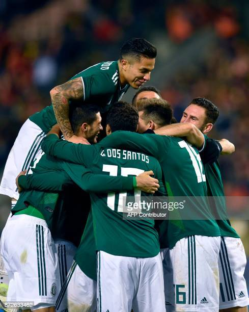 Mexico's forward Hirving Lozano celebrates with teammates after scoring a goal during the international friendly football match between Belgium and...
