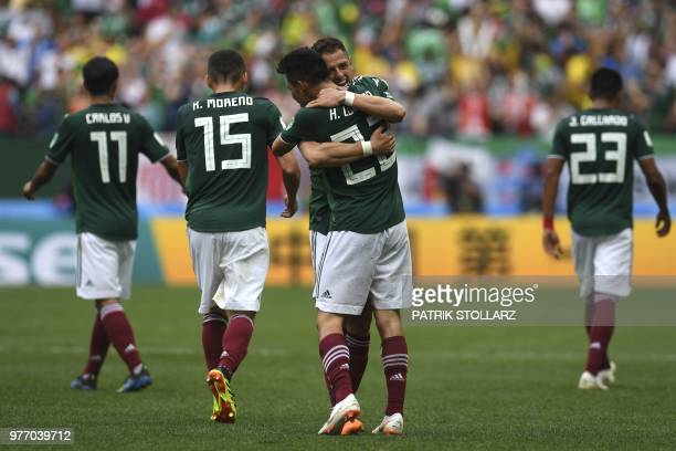 Mexico's forward Hirving Lozano is is congratulated by Mexico's forward Javier Hernandez as he celebrates with teammates after scoring a goal during...