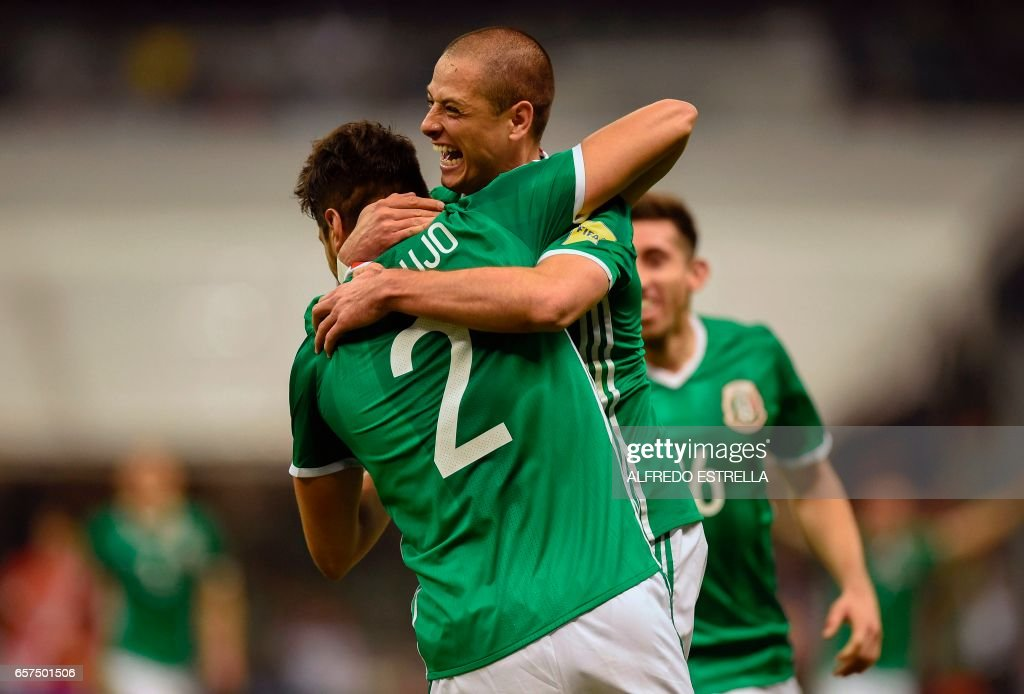 Mexico's forward Javier Hernandez (back) celebrates with teammate Nestor Araujo after scoring against Costa Rica during their 2018 FIFA World Cup qualifier football match in Mexico City on March 24, 2017. /