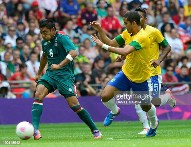 Mexico's forward Marco Fabian runs with the ball followed by Brazil's defender Romulo and Brazil's defender Alex Sandro during the men's football...