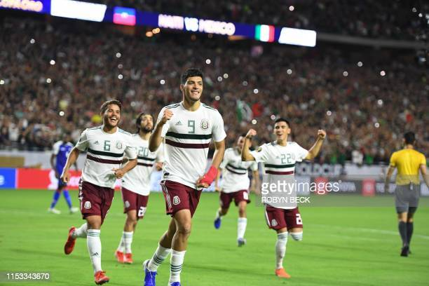 Mexico's forward Raul Jimenez celebrates with teammates after scoring a penalty goal in overtime during the 2019 Concacaf Gold Cup semifinal football...
