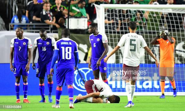 Mexico's forward Raul Jimenez holds his ankle as Haiti's players and Haiti's goalkeeper Johny Placide react to the referee's call for a penalty...