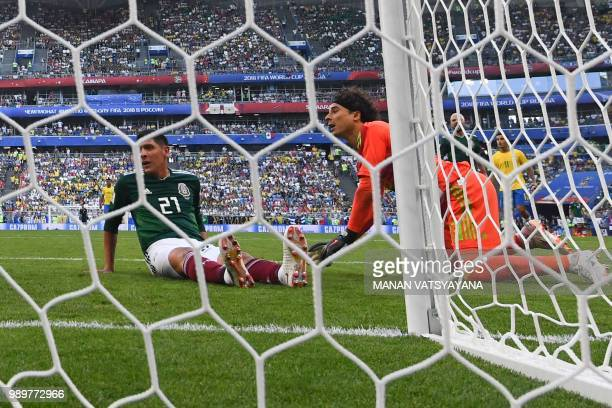 Mexico's goalkeeper Guillermo Ochoa and Mexico's defender Edson Alvarez react as Brazil's forward Neymar scores a goal during the Russia 2018 World...