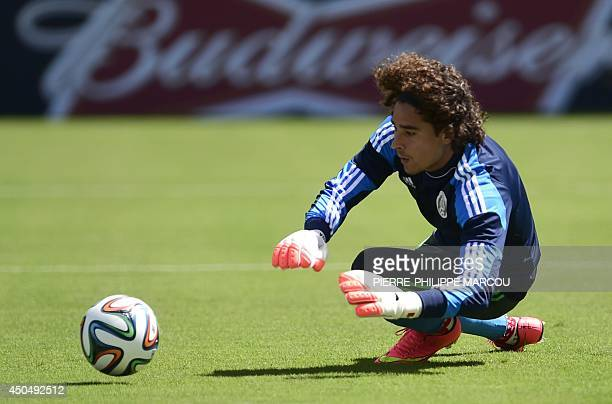 Mexico's goalkeeper Guillermo Ochoa dives for a ball during a training session at the Das Dunas stadium in Natal on June 12, 2014 on the eve of their...