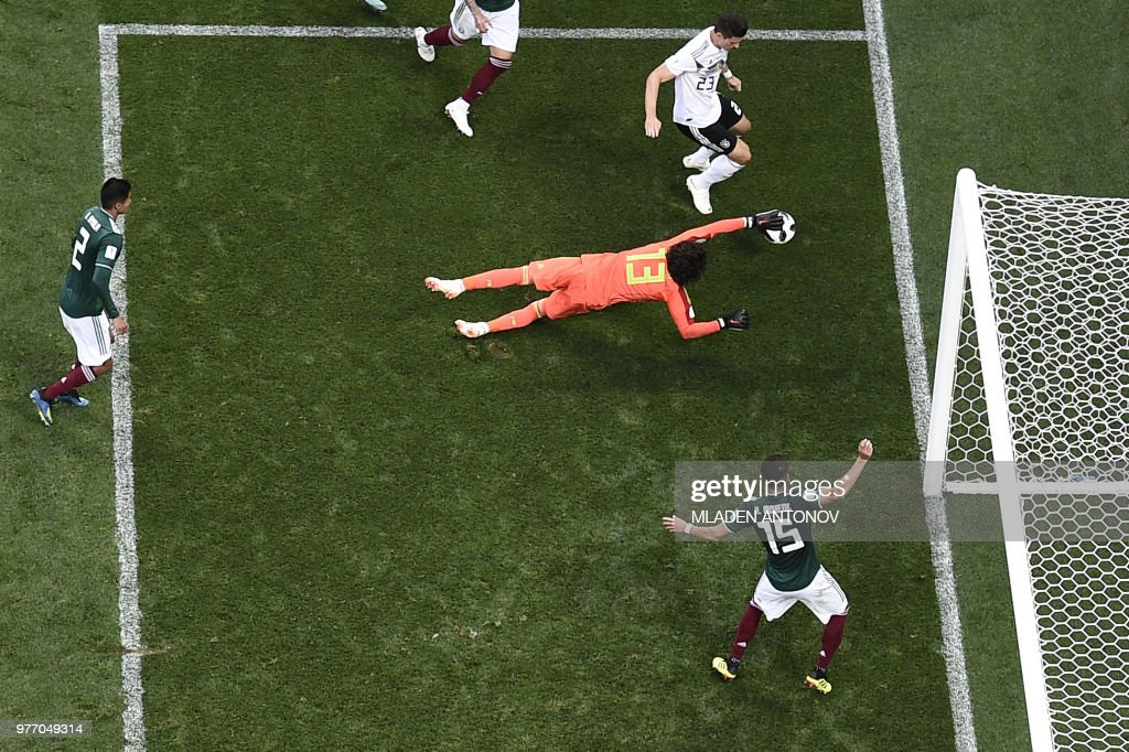 TOPSHOT - Mexico's goalkeeper Guillermo Ochoa (C) dives to save a shot by Germany's forward Mario Gomez during the Russia 2018 World Cup Group F football match between Germany and Mexico at the Luzhniki Stadium in Moscow on June 17, 2018. (Photo by Mladen ANTONOV / AFP) / RESTRICTED