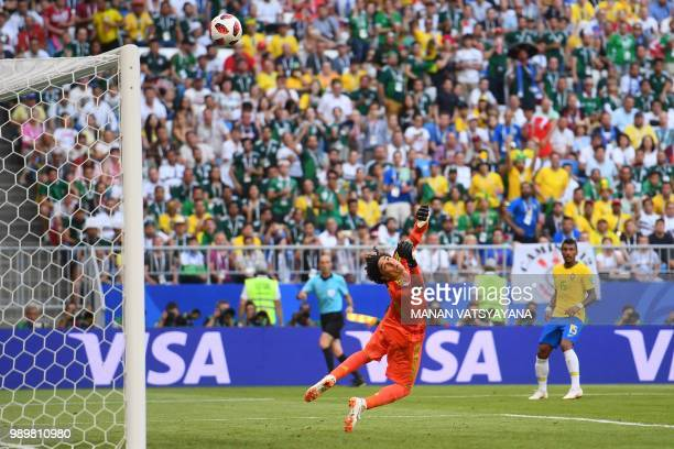 Mexico's goalkeeper Guillermo Ochoa eyes the ball as he jumps to catch it during the Russia 2018 World Cup round of 16 football match between Brazil...