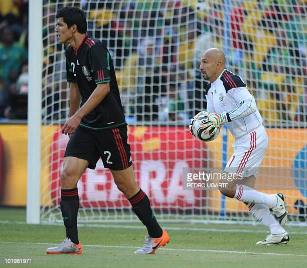 Mexico's goalkeeper Oscar Perez runs with the ball as Mexico's defender Francisco Rodriguez looks at the field during their Group A first round 2010...