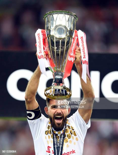 Mexico's Guadalajara Miguel Basulto holds the trophy following victory over Canada's Toronto FC in their final second leg football match of the...