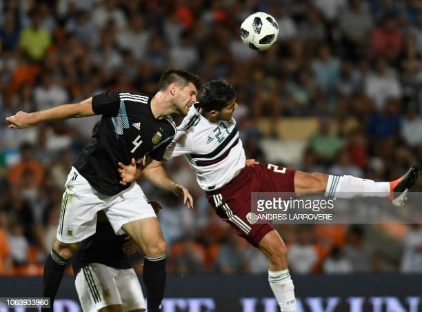 Mexico's Henry Martin vies for the ball with Argentina's Walter Kannemann during their friendly football match at Malvinas Argentinas stadium in...