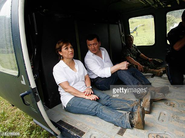 Mexico's Interior Minister Miguel Osorio Chong and Social Development Secretary Rosario Robles sit on the floor of a military helicopter during a...