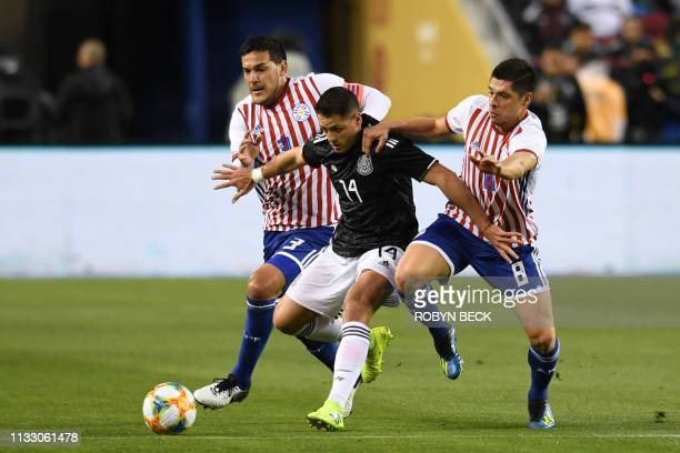 Mexico's Javier Hernandez fights for the ball with Paraguay's Rodrigo Rojas and Gustavo Gomez during the international friendly match between Mexico...