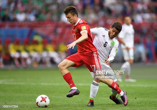 Mexico's Jonathan Dos Santos and Russia's Alexandr Golovin vie for the ball during the group stage match pitting Mexico against Russia at the Kazan...