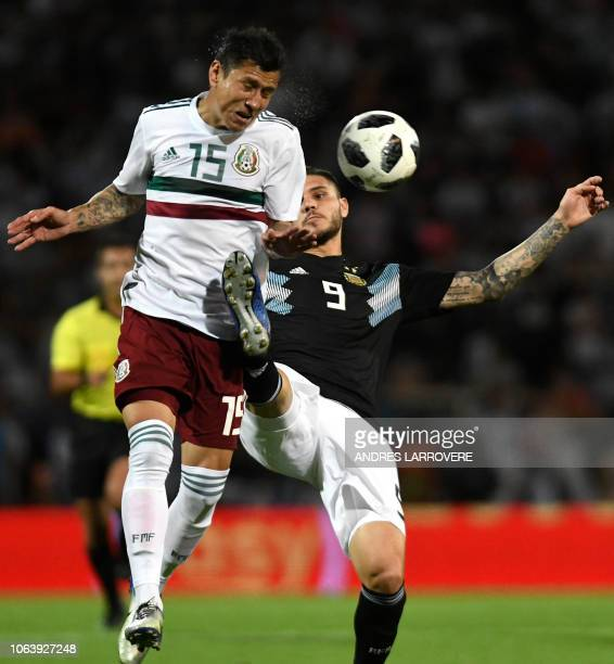 Mexico's Julio Dominguez vies for the ball with Argentina's Mauro Icardi during their friendly football match at Malvinas Argentinas stadium in...