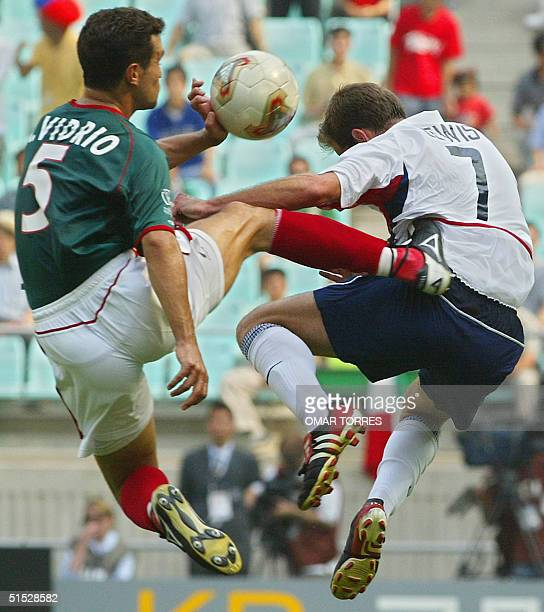 Mexico's Manuel Vidrio gets his studs into the USA's Eddie Lewis , 17 June 2002 at the Jeonju World Cup Stadium in Jeonju, during second round...
