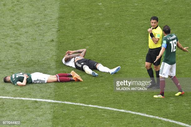 Mexico's midfielder Andres Guardado speaks to Iranian referee Alireza Faghani following a challenge between Mexico's forward Javier Hernandez and...
