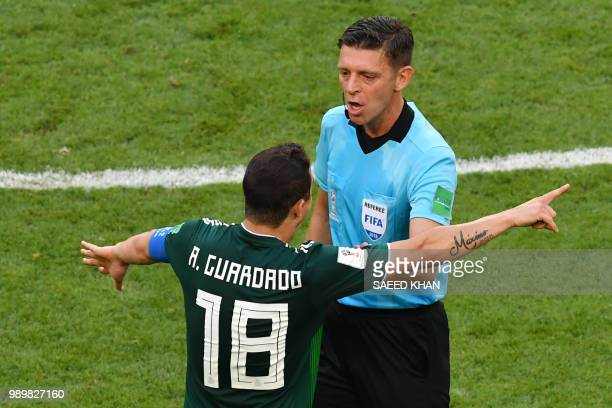 Mexico's midfielder Andres Guardado speaks to Italian referee Gianluca Rocchi during the Russia 2018 World Cup round of 16 football match between...