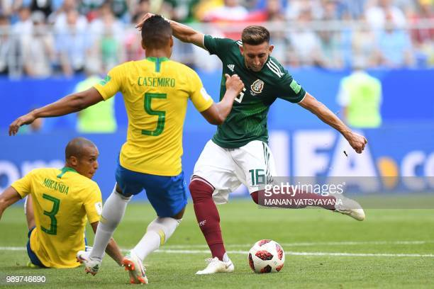 Mexico's midfielder Hector Herrera vies for the ball with Brazil's midfielder Casemiro next to Brazil's defender Miranda during the Russia 2018 World...
