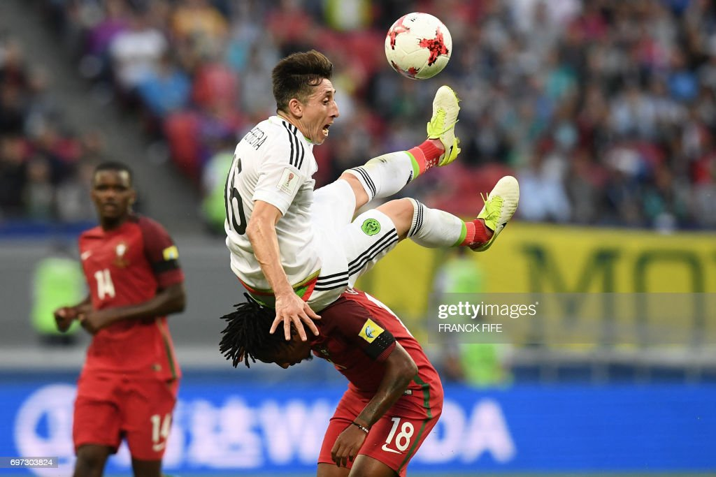 TOPSHOT - Mexico's midfielder Hector Herrera vies with Portugal's forward Gelson Martins (bottom) during the 2017 Confederations Cup group A football match between Portugal and Mexico at the Kazan Arena in Kazan on June 18, 2017. /