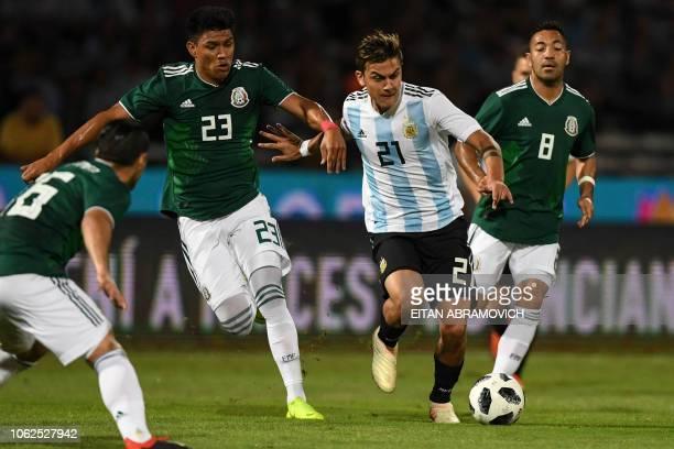 Mexico's midfielder Jesus Gallardo vies for the ball with Argentina's forward Paulo Dybala during their friendly football match at Mario Alberto...