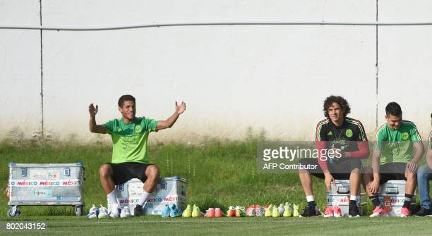 Mexico´s midfielder Jesus Molina sits on a box close to Mexico's goalkeeper Rodolfo Cota during a training session at the Fisht Stadium in Sochi on...