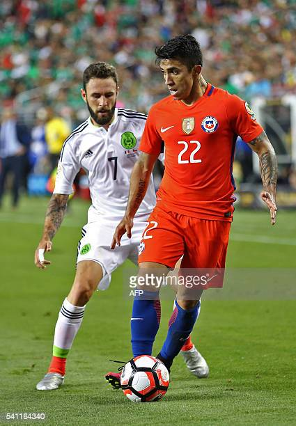 Mexico's Miguel Layun vies for the ball with Chile's Edson Puch a Copa America Centenario quarterfinal football match in Santa Clara California...